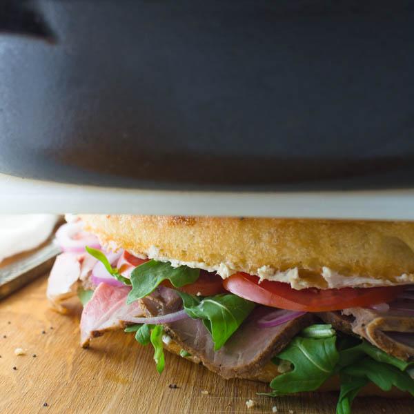 pressing best roast beef sandwich under a cast iron skillet.