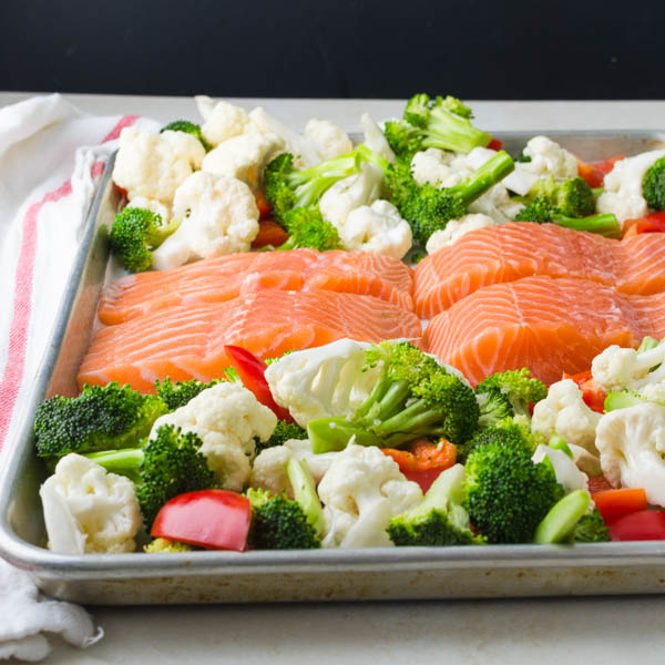 arranging salmon and vegetables on a half sheet pan.