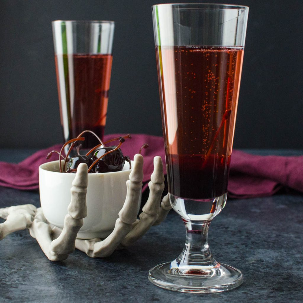 Bloody champagne Bellinis and a skull hand holding Amarena cherries.