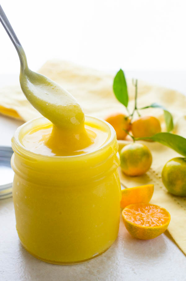 dunking a spoon into calamondin fruit curd.