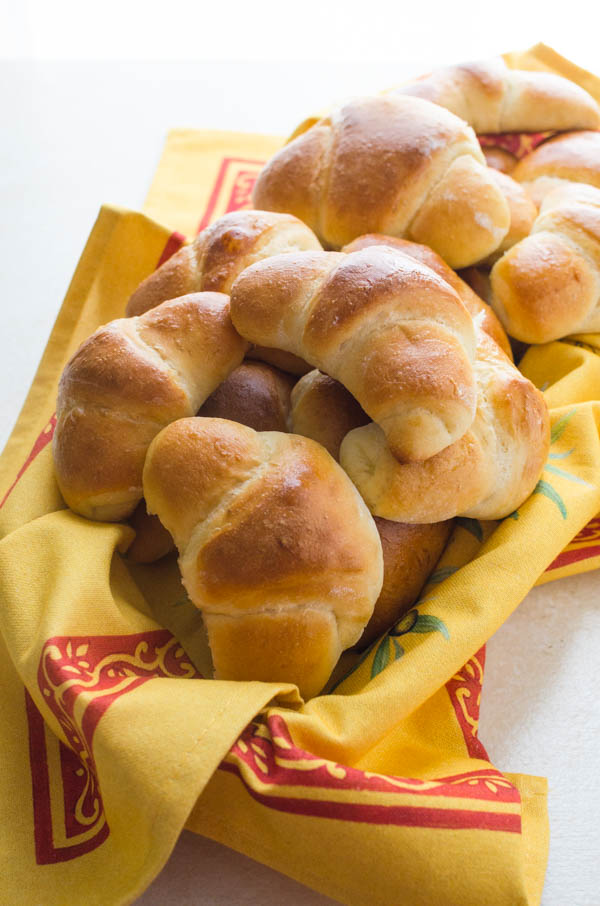 Homemade crescent rolls in a bread basket.
