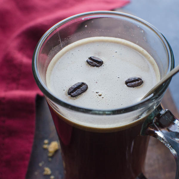 Coffee Hot Buttered Rum with floating coffee beans on top.