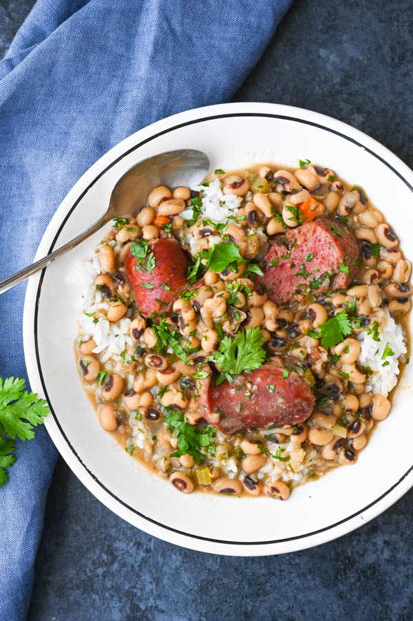 New Years Recipes for dinner: Hoppin John Soup in a bowl with spoon and rice.