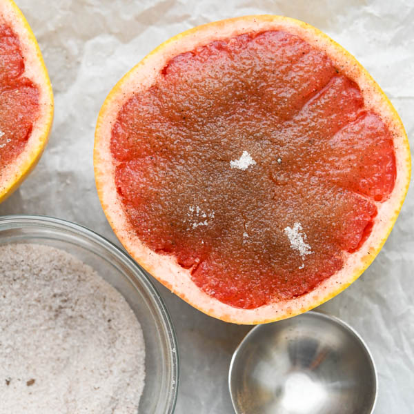 Sprinkling fruit with spice blend to make broiled grapefruit.