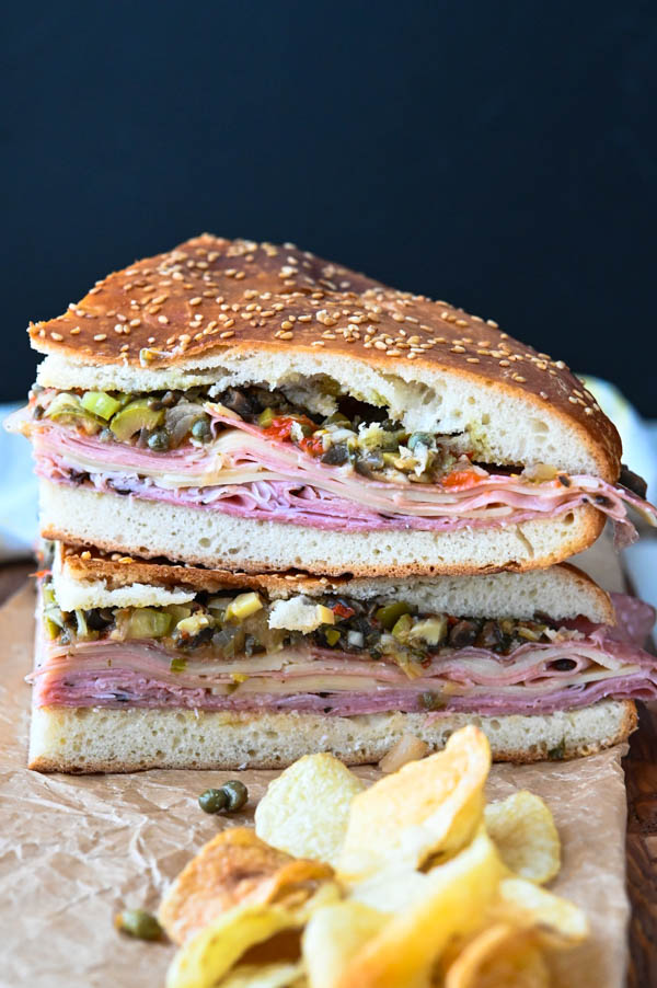 slicing the muffuletta sandwich recipe into quarters and serving with chips.