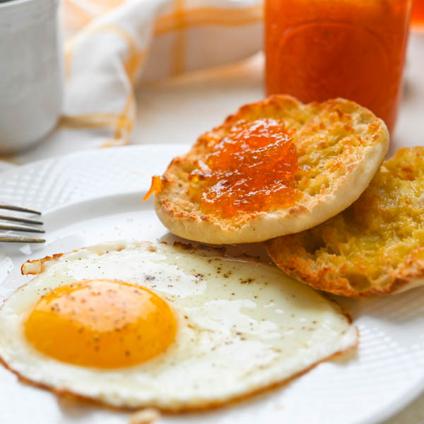 citrus marmalade on an english muffin with morning eggs and coffee.