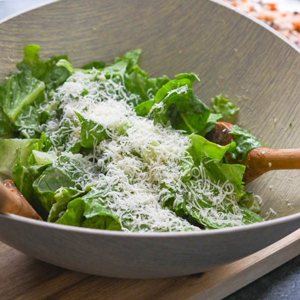 adding dressing and parmigiano reggiano to romaine lettuce.