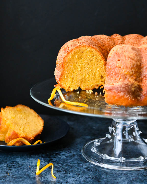 Orange bundt cake on a cake stand with a slice taken out.