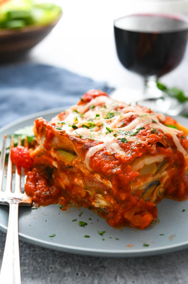 A slice of hearty lasagna on a plate with red wine and green salad in the background.