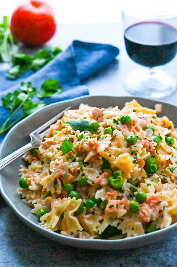 RoseMarie's Best Smoked Salmon with Cognac Cream Pasta in a serving bowl with a glass of wine.