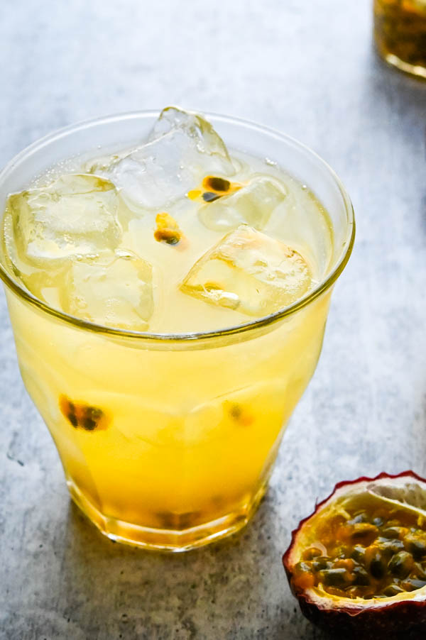 A glass of sparkling lemonade with a passion fruit beside it.