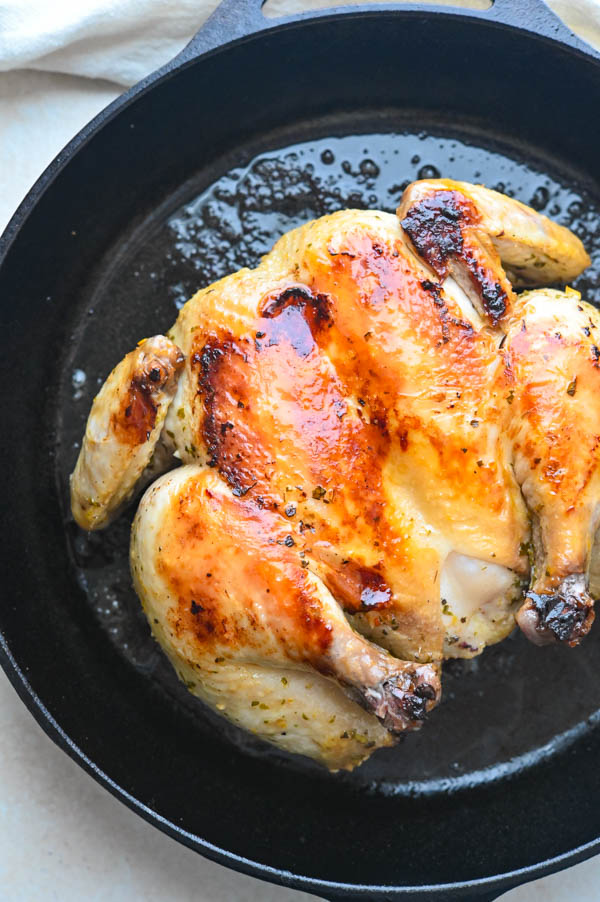 butterflied roast chicken in a cast iron skillet