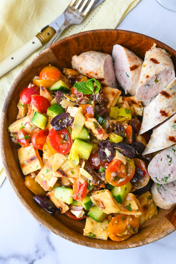 Serving the grilled panzanella salad with chunked chicken spinach feta sausages alongside.