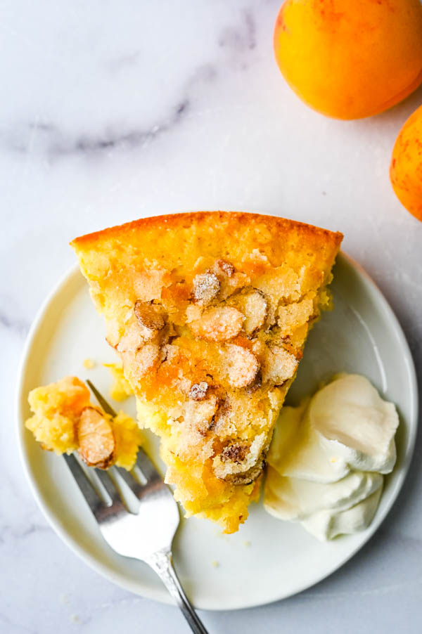 a slice of apricot dessert with sugared almonds on a plate with whipped cream.