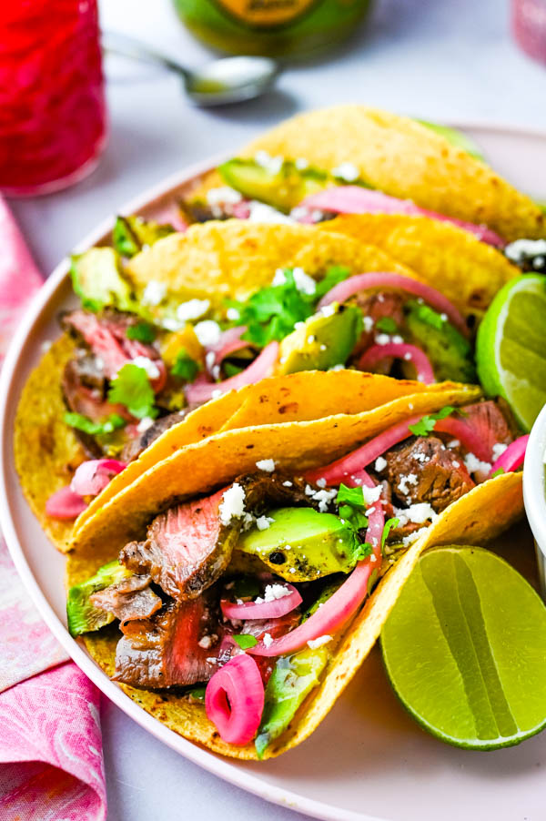 Carne asada tacos recipe with wedges of lime, grilled avocados and pink pickled onions.