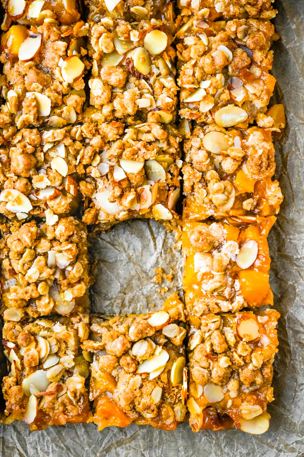 cutting the peach bars with streusel topping into squares.