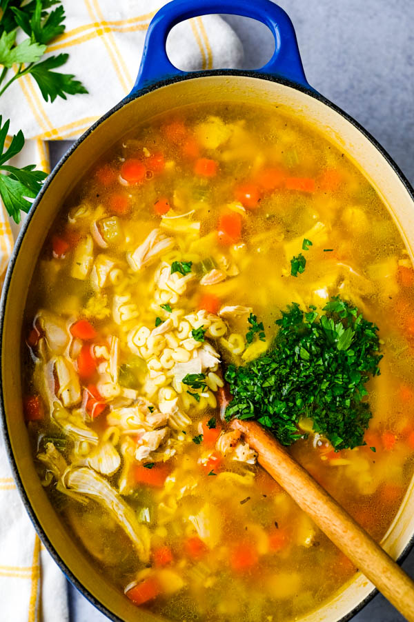 Leftover turkey alphabet soup with fresh parsley in a dutch oven.