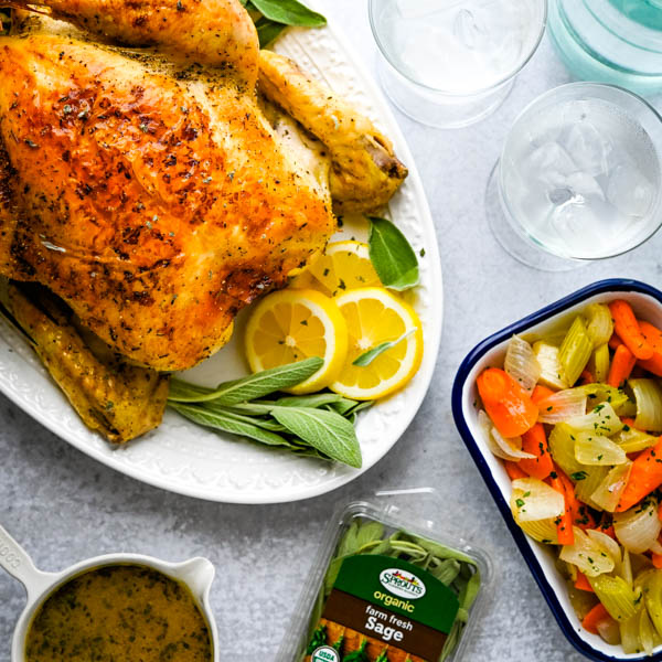 serving herb roasted chicken with roast chicken gravy and vegetables.