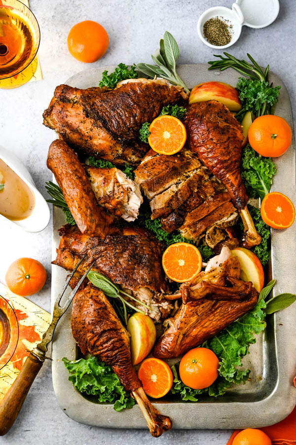 Carved dry brine turkey on a platter with mandarins, kale and herbs.