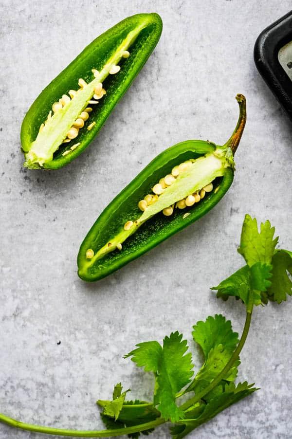 jalapeños cut in half with cilantro for fresh tomato salsa recipe.