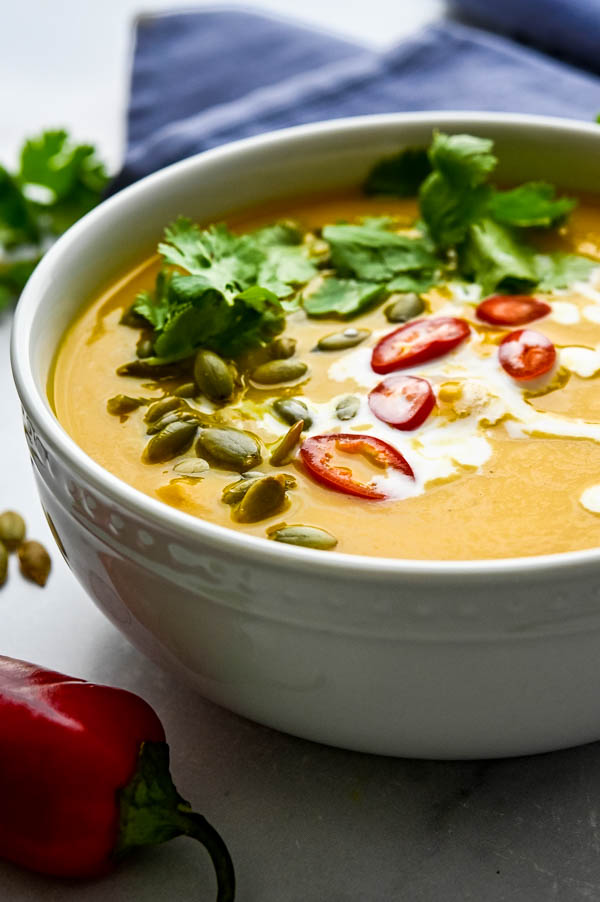 Garnishing thai style creamy pumpkin soup with cilantro, chiles and pumpkin seeds.