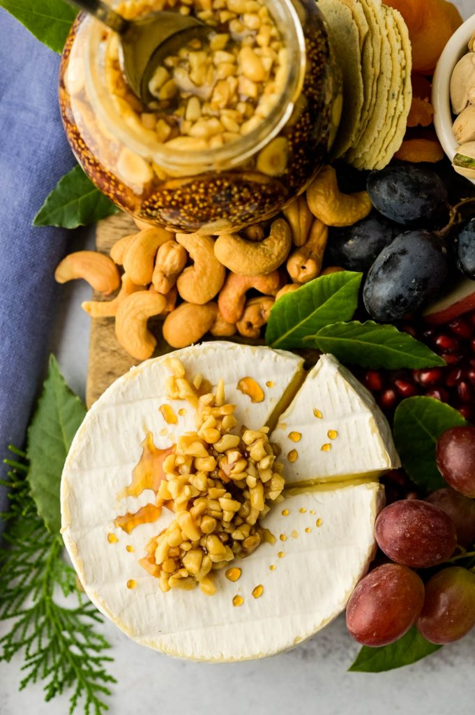 best cheeses for cheese board starts with everyone's favorite brie, topped with honeyed nuts.
