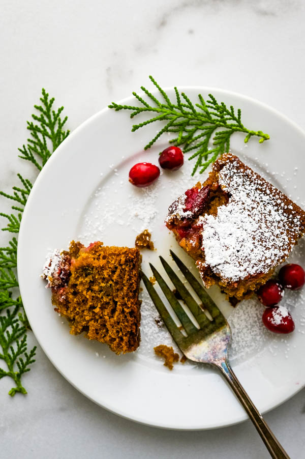 A piece of ginger cake on a plate with fresh cranberries on the side.