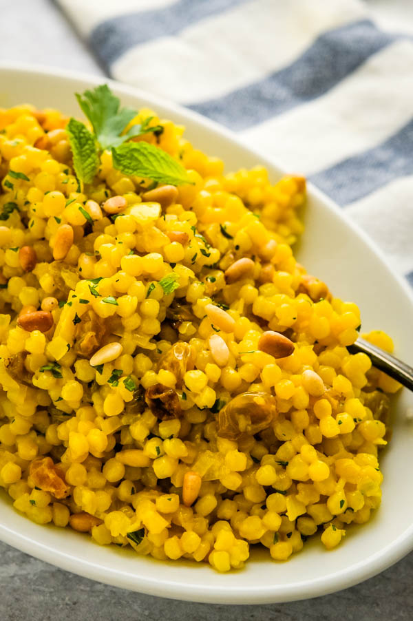 Healthy Turmeric couscous with a mint leaf.