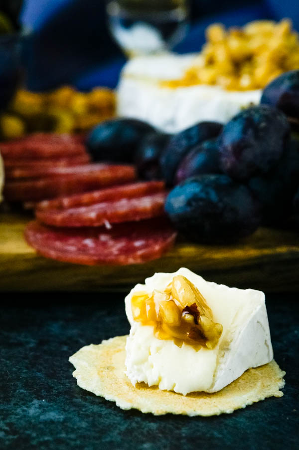 Cracker with brie and honeyed nuts from the cheese and charcuterie board.