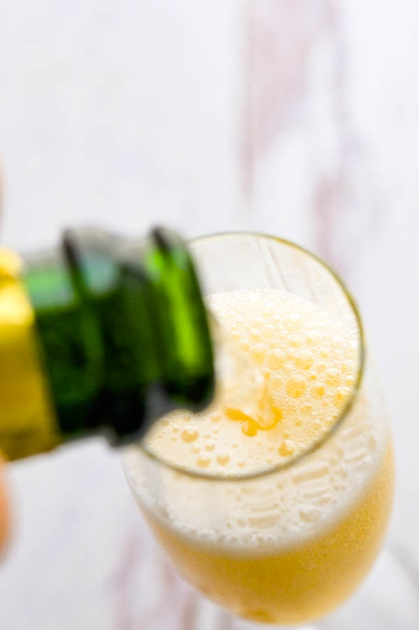 topping the honey syrup and elderflower drink with prosecco