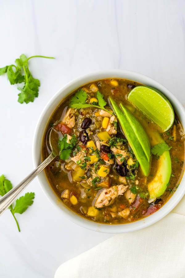 A bowl of chicken taco soup with black beans and a wedge of lime.