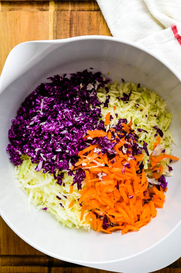 adding grated red cabbage and carrot to the green cabbage slaw