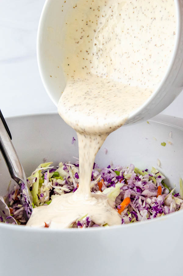 Pouring the sweet and tangy dressing over the cabbage slaw mixture.