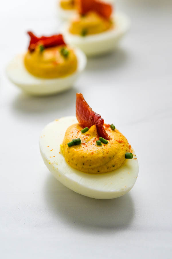 Healthy deviled egg with a small slice of country ham and chives.
