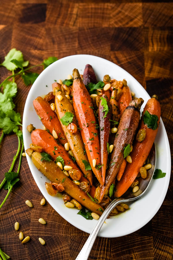 Serving Moroccan carrots with pine nut and cilantro garnish on a serving plate.