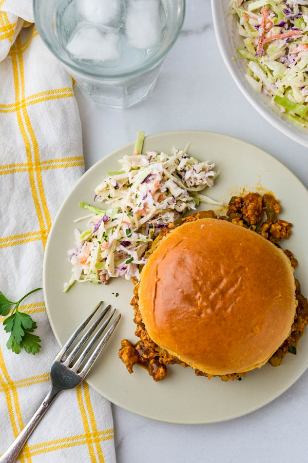 homemade loose meat sandwich on a bun served with coleslaw.