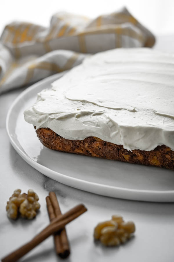 frosted square carrot cake on a platter.