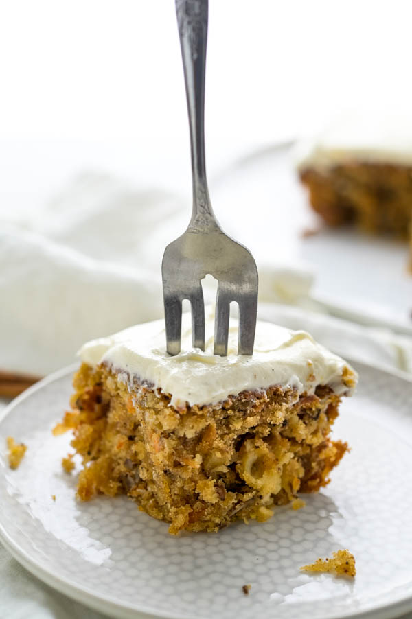 A fork in a slice of the carrot walnut cake.