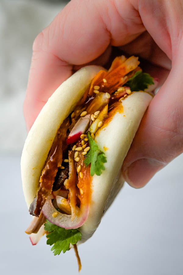 holding Chinese bbq pork buns to eat.