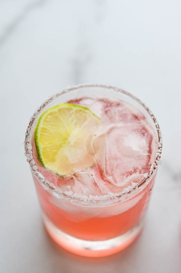 Serving the margarita on the rocks in a cocktail glass with lime slice.