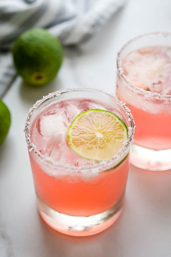 Adding a lime garnish to the hibiscus margarita with salted rim.