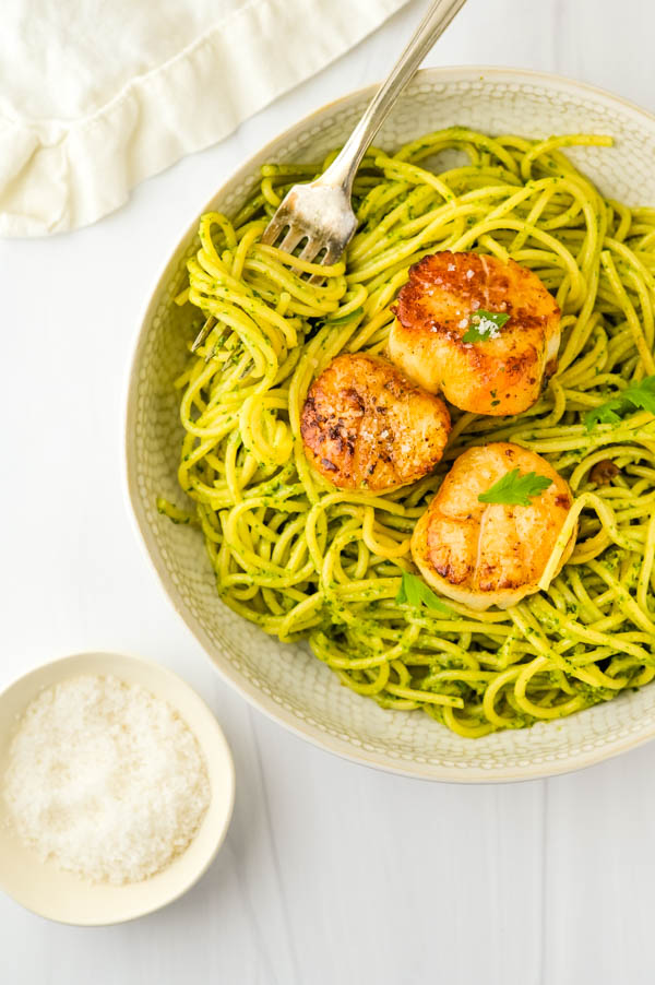 Topping the spinach pesto pasta with pan seared dry scallops.