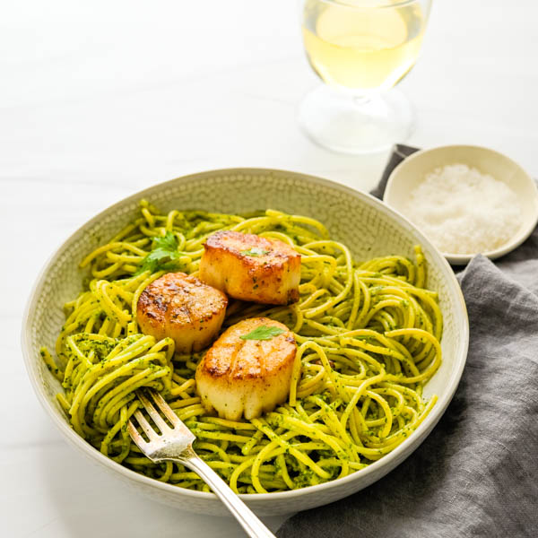 Pan seared scallops with spinach pesto pasta in a bowl with a fork.