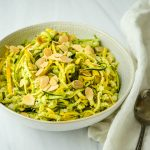 Prepared courgette salad with pesto vinaigrette in a serving bowl with a spoon.