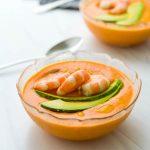 A bowl of salmorejo soup recipe topped with avocado and shrimp.