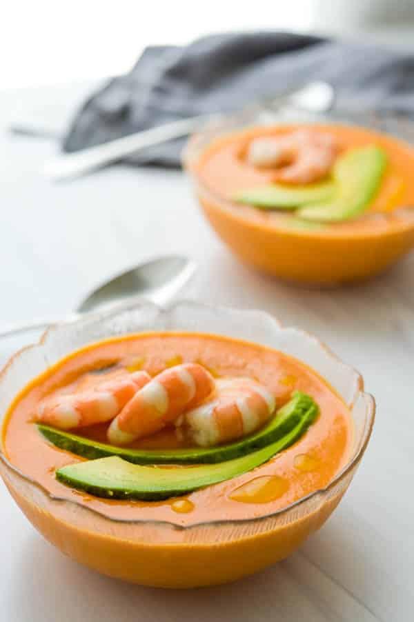 Cold tomato soup with optional avocado and shrimp garnish.