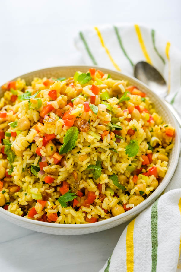 Curried Rice Salad in a bowl with fresh mint leaves.
