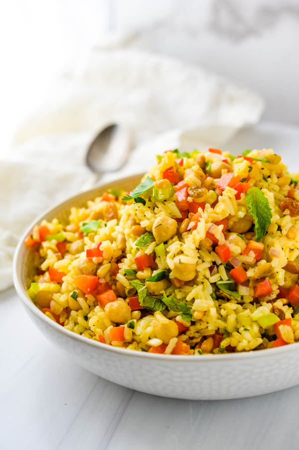 A photo of the curried rice salad in a bowl with a spoon and napkin in the background.