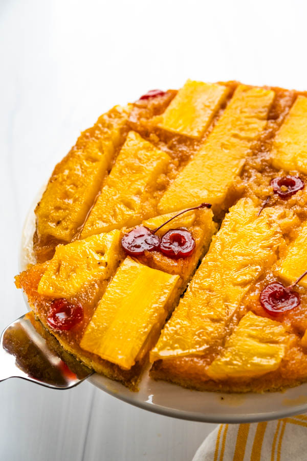 removing a slice of pineapple rum cake with a server.