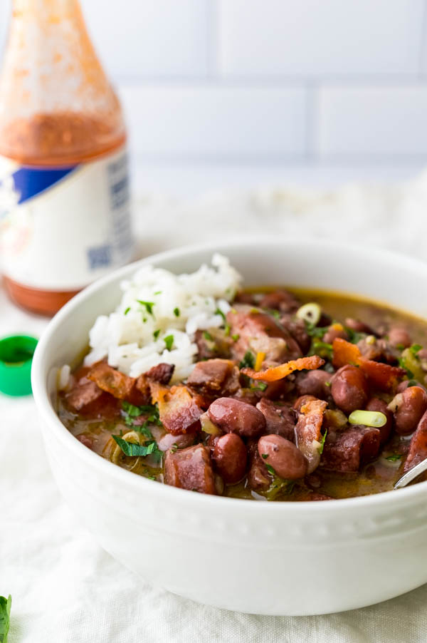 a serving of red beans rice and sausage in a bowl with hot sauce.